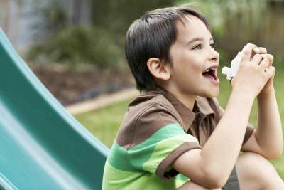 child on a slide with an inhaler
